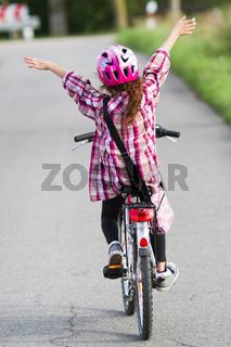 Mädchen fährt freihändig Fahrrad