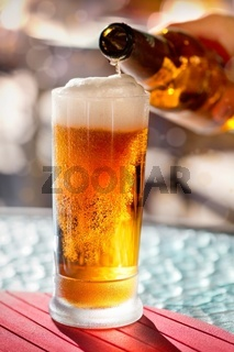 Pouring beer into mug from the bottle