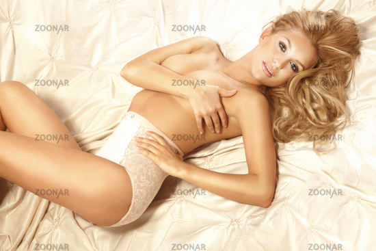 Amazing young sensual woman with long blonde hair in bed