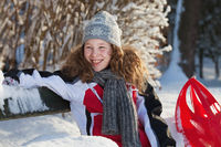 Girl in winter cloths with red sledge
