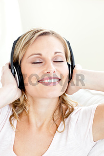 Radiant young woman listening to music wearing headphones