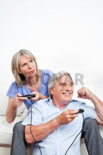 Senioren spielen mit Spielekonsole