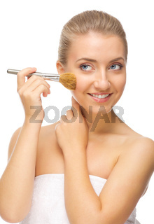 Young smiling woman with makeup brush