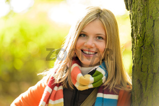 Smiling teenager blonde girl woods tree autumn