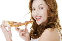 Happy woman eating pizza.
