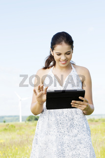 Teen girl with tablet computer next to wind turbine.