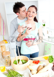 Loving couple preparing a salad in the kitchen and drinkng wine