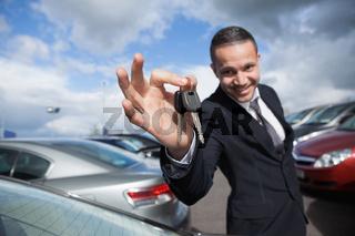 Happy dealer holding car keys