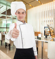 young chef with thumb up gesture in the restaurant