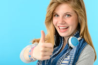 Cheerful teenage girl showing thumbs up