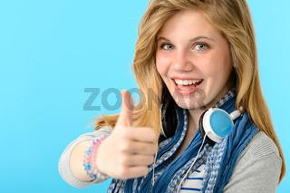 Cheerful teenage girl showing thumbs up