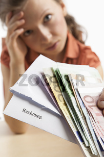 Verzweifelte Frau hält Geld und Rechnung in der Hand