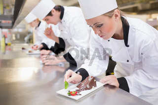 Chef's team garnishing slices of cake