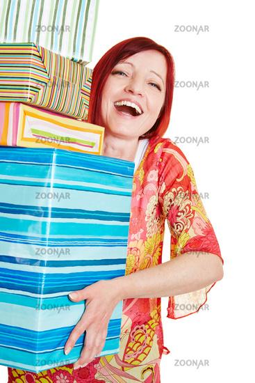 Lachende Frau trägt viele Geschenke