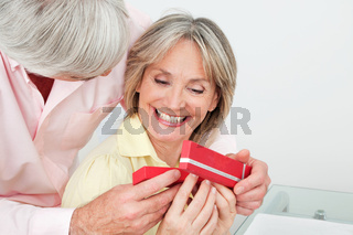 Lachende Seniorin bekommt Geschenk