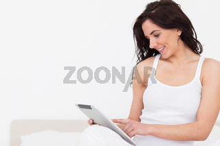 Smiling brunette woman sitting while using her touchscreen
