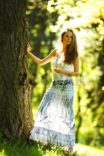 girl standing next to a tree portrait