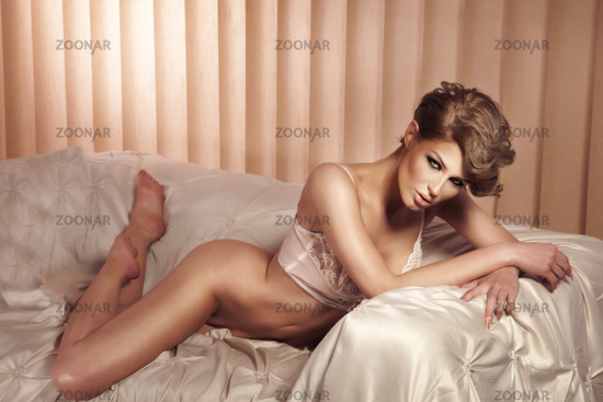 Fashionable photo of young elegant woman in bed