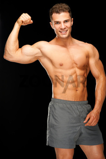 Portrait of confident muscular man flexing his biceps