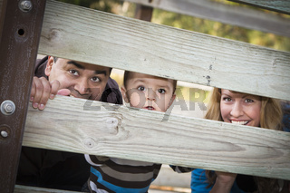 Happy Young Mixed Race Ethnic Family Looking Through Fence
