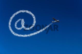 Flugzeug schreibt at-Zeichen in den Himmel