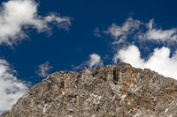 Felsiger Berggipfel unter blauem Himmel und weissen Wolken / Rocky mountain peak under blue sky with withe clouds