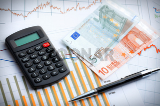 Calculator and euro currency on business graph.