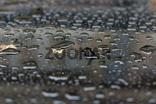 Wassertropfen auf einer Autofensterscheibe
