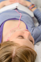 Lying girl relaxing and listening to music