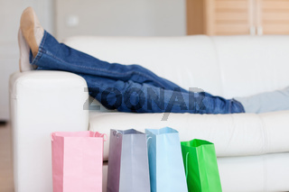 Female legs resting on sofa after shopping tour