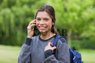 Young smiling girl talking on the phone while standing upright in the countryside