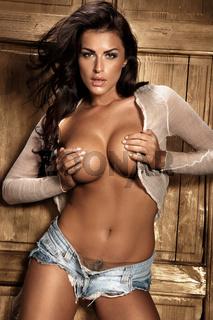 Studio shot of sexy brunette girl covering her breast.