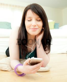 Dreamy woman listening music lying on the floor