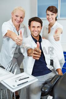 Team beim Zahnarzt hält Daumen hoch