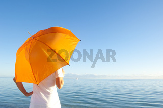 Woman with orange umbrella at ocean background