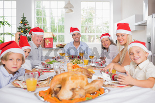 Smiling family around the dinner table at christmas