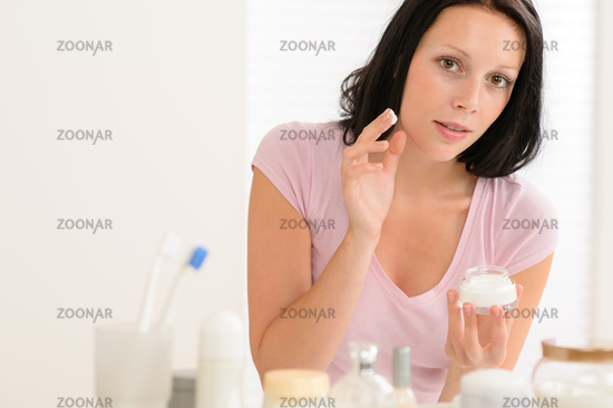 Beauty woman put moisturizer cream in bathroom