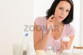 Beauty woman put moisturizer cream in bathroom