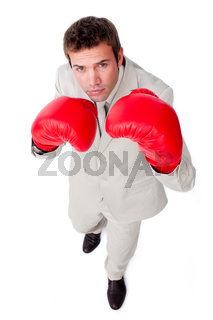 Confident young businessman checking out the competition against a white background