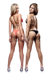 Two beautiful athletic girl wearing bikini posing over white background