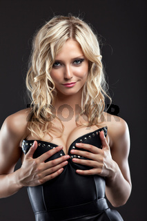 Sexy blond woman in leather corset take breast