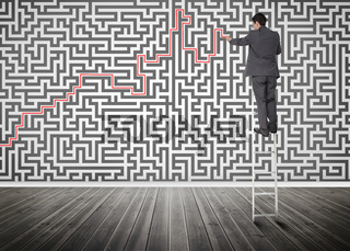 Businessman standing on a ladder solving maze puzzle