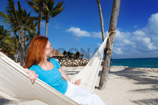 woman in hammock on background of ocean and sky
