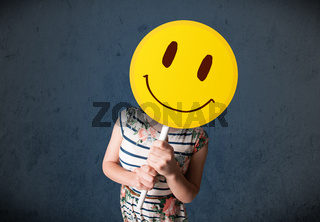 Young woman holding a smiley face emoticon
