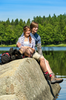 Young couple hikers lounging at lake nature