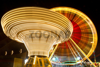 Ferris wheel and carousel at county fair at night, Karlsruhe, Germany