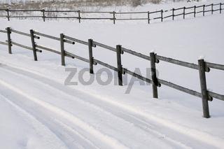Zäune und Fahrspur im Schnee