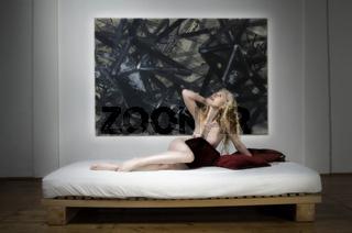 Nackte blonde Frau liegt auf einem Bett mit Polstern