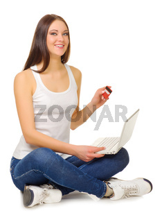 Young girl with laptop and credit card isolated