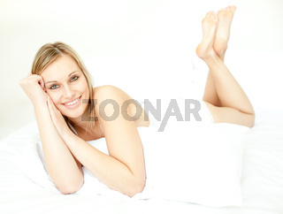 Radiant blond woman lying down on bed